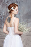 Young red-haired bride in elegant wedding dress. She stands with her back to the viewer. Her eyes are dreamy closed. Royalty Free Stock Photos