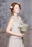 Young red-haired bride in pearl-gray dress. She stands, her eyes are dreamy closed, she is holding a bouquet of white wildflowers. Stock Photo