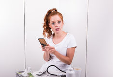 Young red-haired female doctor looks worried at diagnosis result Royalty Free Stock Image