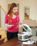 Young red haired female with electric slow cooker in kitchen at Royalty Free Stock Photo