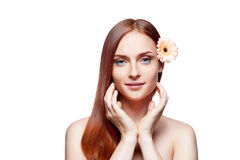 Young red-haired female with flower in hair. Horizontal studio beauty portrait of young attractive green-eyed red-haired caucasian female with beige gerbera stock photography
