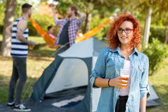 Young red-haired female with glasses posing with glass of beer Royalty Free Stock Images