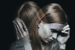 Female with mood disorder. Young red haired female with mood disorder crying and having a headache royalty free stock photography
