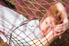 Young red-haired female relaxing in hammock. Beautiful red-haired female relaxing in a hammock, looking into the camera Stock Photo