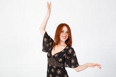 Young red-haired girl in a black dress dancing. Royalty Free Stock Photos