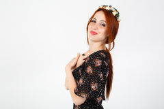 Young red-haired girl in a black dress dancing. Stock Photos