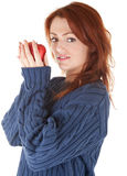 Young red-haired girl in a blue sweater with an ap Royalty Free Stock Photos