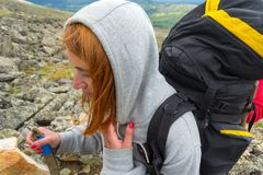 Young red-haired girl climber during a climb up the mountain wit royalty free stock photography