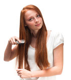 Young red-haired girl combing her long hair. Isolated on white b Royalty Free Stock Images