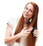 Young red-haired girl combing her long hair. Isolated on white b Royalty Free Stock Photography