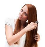 Young red-haired girl combing her long hair. Isolated on white b Stock Photos