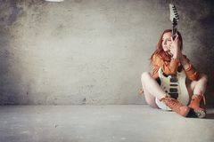 Young red-haired girl with an electric guitar. Rock musician gir. Young red-haired girl with electric guitar. Rock musician girl in a leather jacket. She is a Stock Photography