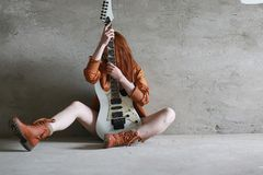 Young red-haired girl with an electric guitar. Rock musician gir. Young red-haired girl with electric guitar. Rock musician girl in a leather jacket. She is a Royalty Free Stock Photos