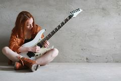 Young red-haired girl with an electric guitar. Rock musician gir. Young red-haired girl with electric guitar. Rock musician girl in a leather jacket. She is a Stock Images