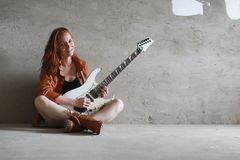 Young red-haired girl with an electric guitar. Rock musician gir. Young red-haired girl with electric guitar. Rock musician girl in a leather jacket. She is a Royalty Free Stock Images