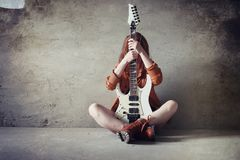 Young red-haired girl with an electric guitar. Rock musician gir. Young red-haired girl with electric guitar. Rock musician girl in a leather jacket. She is a Stock Image