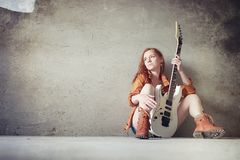 Young red-haired girl with an electric guitar. Rock musician gir. Young red-haired girl with electric guitar. Rock musician girl in a leather jacket. She is a Royalty Free Stock Photography