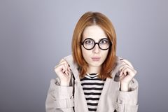 Young red-haired girl in glasses and cloak. Stock Images