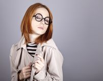 Young red-haired girl in glasses and cloak. Royalty Free Stock Photography
