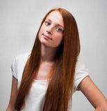 Young red-haired girl on gray background Royalty Free Stock Images