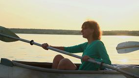 Young red-haired girl paddling kayak at sunset. Sport, tourism. Stock footage stock video