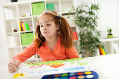 Young red-haired girl with pigtails drawing with watercolors on Royalty Free Stock Photos