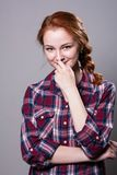 Young red-haired girl in a plaid shirt with fingers on his lip Royalty Free Stock Images