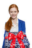 Young red haired Girl presenting a gift. Young red haired businesswoman presents present with a big smile Stock Photos