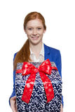 Young red haired Girl presenting a gift. Young red haired businesswoman presents present with a big smile Royalty Free Stock Photo