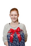 Young red haired Girl presenting a gift. Young well dressed red haired Girl presents present with a big smile Royalty Free Stock Images