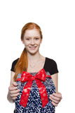 Young red haired Girl presenting a gift. Young well dressed red haired Girl presents present with a big smile Royalty Free Stock Image