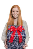 Young red haired Girl presenting a gift. Young well dressed red haired Girl presents present with a big smile Stock Photo