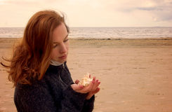 Young red-haired girl sits on a fishing net and looks at a seashell in her hands Stock Photos
