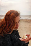 Young red-haired girl sits on a fishing net and looks at a seashell in her hands Royalty Free Stock Image