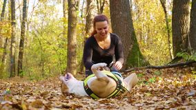 Happy girl petting dog American Staffordshire terrier in autumn forest