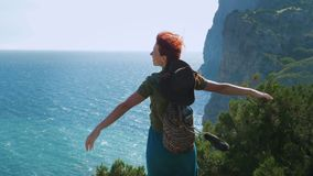 A young red-haired girl traveler with a cowboy hat and a backpack stands on the top of the mountain, arms outstretched. To the side, and looks at the sea stock video footage