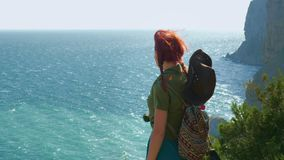 Young red-haired girl traveler in a cowboy hat with a backpack stands on top of the mountain and looks at the blue sea. stock video footage