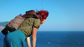 A young red-haired girl traveler with a cowboy hat and backpack stands on top of a mountain and looks down at the sea. stock video footage