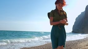 Young red-haired girl traveler with a cowboy hat and a backpack wanders along the sea beach. Young red-haired girl traveler with a cowboy hat and backpack walks stock video footage