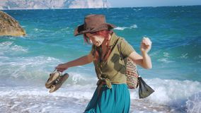 Young red-haired girl traveler with a cowboy hat and a backpack wanders along the sea beach. Young red-haired girl traveler with a cowboy hat and backpack walks stock video