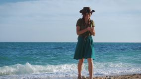 Young red-haired girl traveler with a cowboy hat and a backpack wanders along the sea beach. A young red-haired traveler girl in a cowboy hat and backpack walks stock video footage