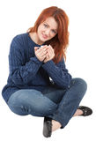 Young red-haired girl with a white cup in hand Royalty Free Stock Photography