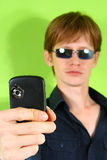 Young red-haired guy with the phone Stock Photos