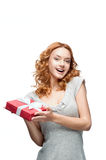 Young red-haired happy smiling girl holding gift. Young red-haired casual european happy smiling girl holding gift Royalty Free Stock Images