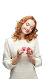 Young red-haired happy smiling girl holding gift. Young red-haired casual european happy smiling girl holding gift Stock Photos