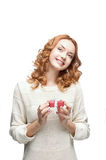 Young red-haired happy smiling girl holding gift. Young red-haired casual european happy smiling girl holding gift Royalty Free Stock Image