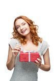 Young red-haired happy smiling girl holding gift. Young red-haired casual european happy smiling dreamy girl holding gift Stock Images