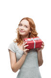 Young red-haired happy smiling girl holding gift. Young red-haired casual european happy smiling dreamy girl holding gift Royalty Free Stock Photography