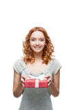 Young red-haired happy smiling girl holding gift. Young red-haired casual european happy smiling girl holding gift Stock Photography