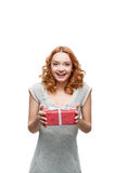 Young red-haired happy smiling girl holding gift. Young red-haired casual european happy smiling girl holding gift royalty free stock photo